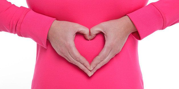 A woman making a heart shape with her hands over her stomach, concept of wellbeing and a healthy lifestyle.