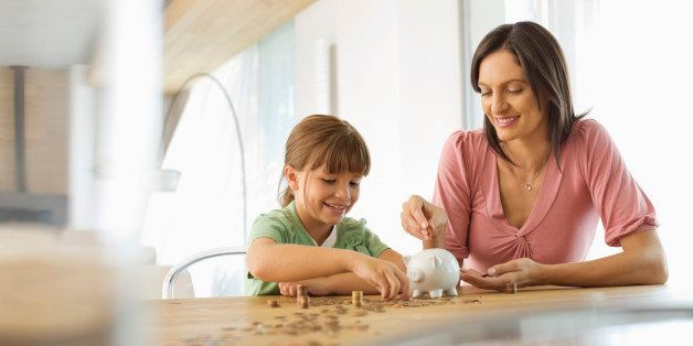 Mother and daughter filling piggy bank