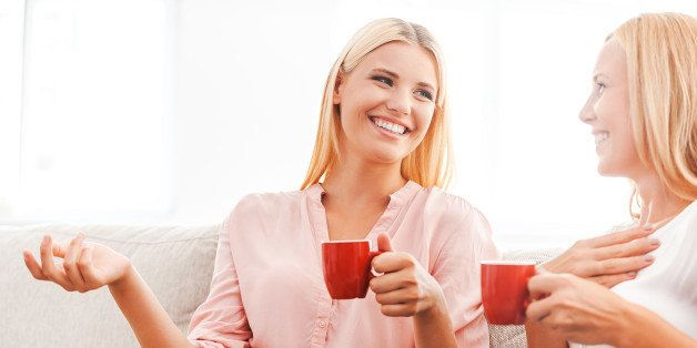 Happy young woman and her mother drinking coffee and talking while sitting on sofa together