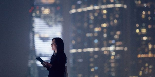 Joyful businesswoman looking away city skyline while using digital tablet, standing against illuminated highrise corporate buildings at night time.
