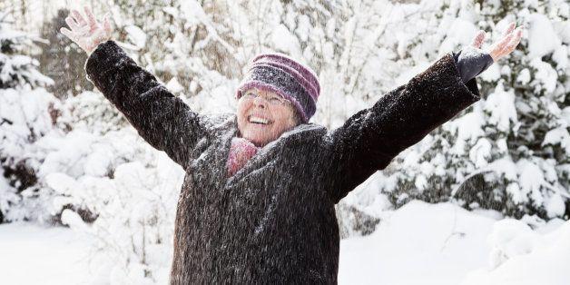healthy senior woman outdoors, enjoying snow and winter