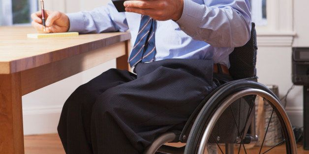Businessman with spinal cord injury in a wheelchair using a smartphone