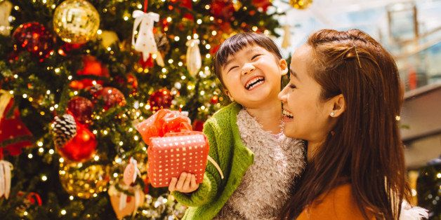 Pretty young mom carrying lovely little daughter who has a beautifully wrapped Christmas present in her hand while they talking to each other joyfully in front of a decorated Christmas tree in the shopping mall