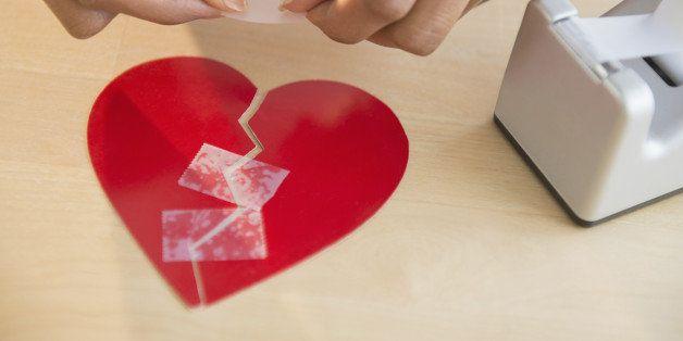 Mixed race woman taking broken paper heart