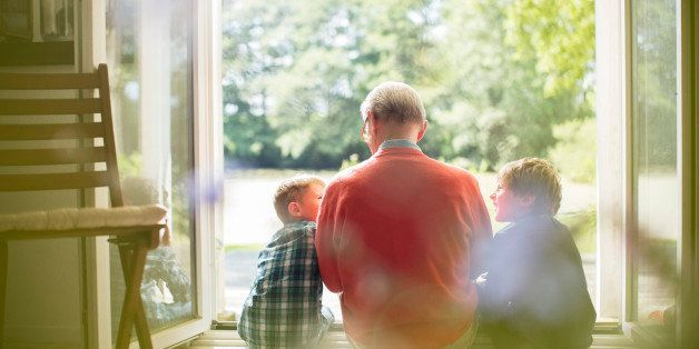 Grandfather and grandsons sitting in doorway