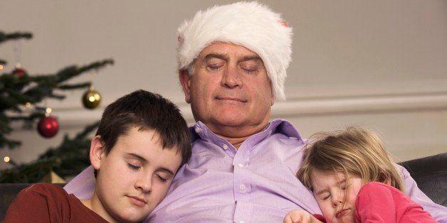 Grandfather and grandchildren asleep on sofa on Christmas