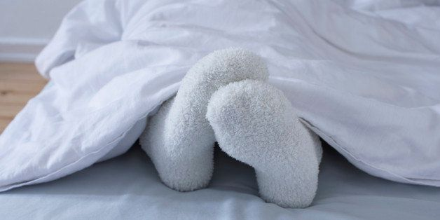 detail of woman lying in bed showing feet in woollen socks
