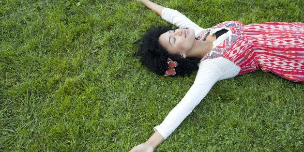 Woman with eyes closed lying on grass