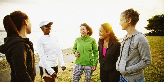 Group of female  friends laughing together after completing run at sunset