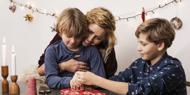 Mother and sons wrapping up Xmas parcel
