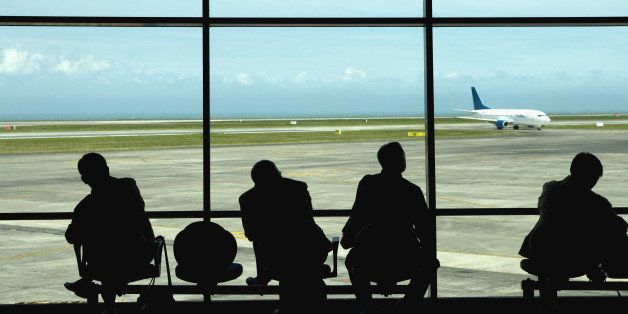 Businessmen watching airplanes on tarmac in airport
