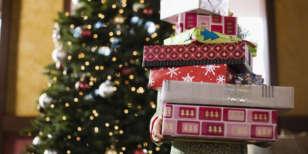 Child holding stack of Christmas gifts