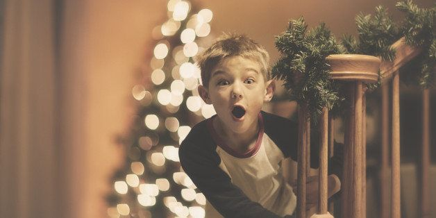 little boy coming down stairs with a surprised expression, Christmas tree in the background.