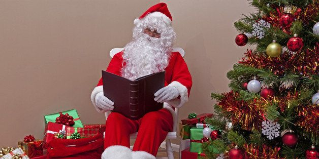 Santa Claus sat in a rocking chair reading the 'naughty or nice' list surrounded by gift wrapped presents.