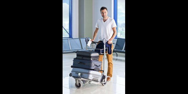 Full lenght portrait of a mid adult man pushing a luggage trolley with suitcases at the airport and smiling at the camera.