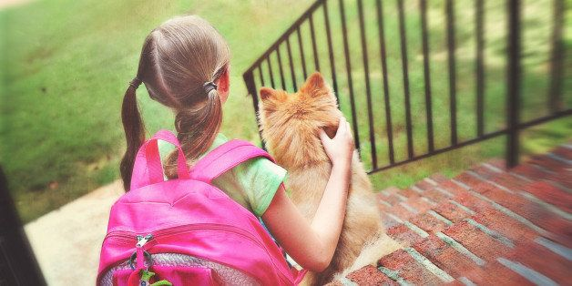 young girl with pink backpack sitting on the steps with her Pomeranian dog in the morning waiting on the school bus