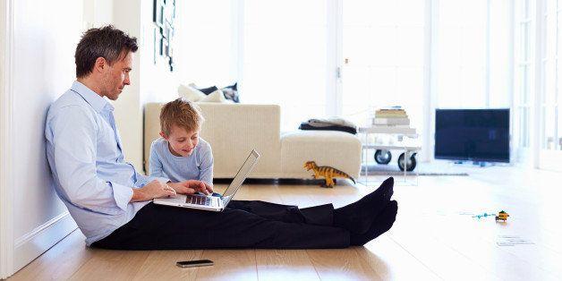 Man sitting on floor using laptop, son watching