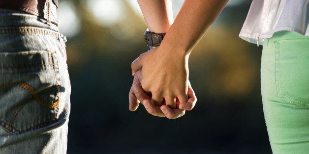 A Young Couple Holding Hands In The Sunset