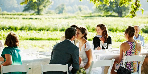 Bride and groom seated at outdoor banquet table about to kiss wedding guests in background