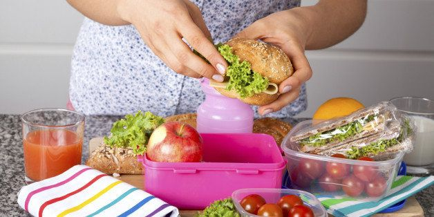 Woman preparing delicious sandwich with cheese and green salad