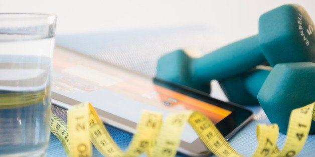 Dumbbells, tape measure and digital tablet