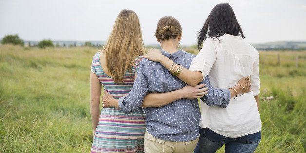 Rear view of female family members walking through field