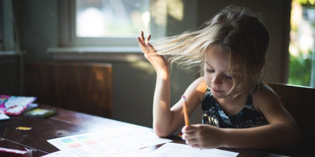A 5 year old girl is sitting at a table and using a pencil to do homework.  She is playing with her hair while concentrating on her work. Some pretty rays of light are shining on her through a window.