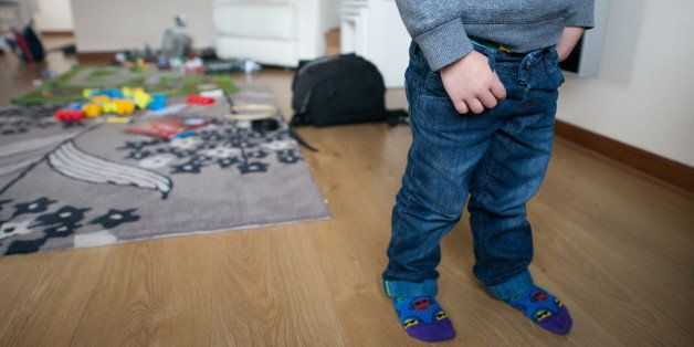 Artistic image of a two year old boy at home with a mess of toys and play things all around him standing.