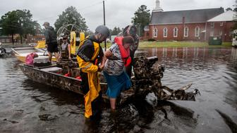 Members of the Cajun Navy help Diana Collazo off a boat after rescuing her family and her from their flooded home in Lumberton, North Carolina on Sunday.