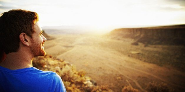 Smiling man looking out over desert canyon at sunset