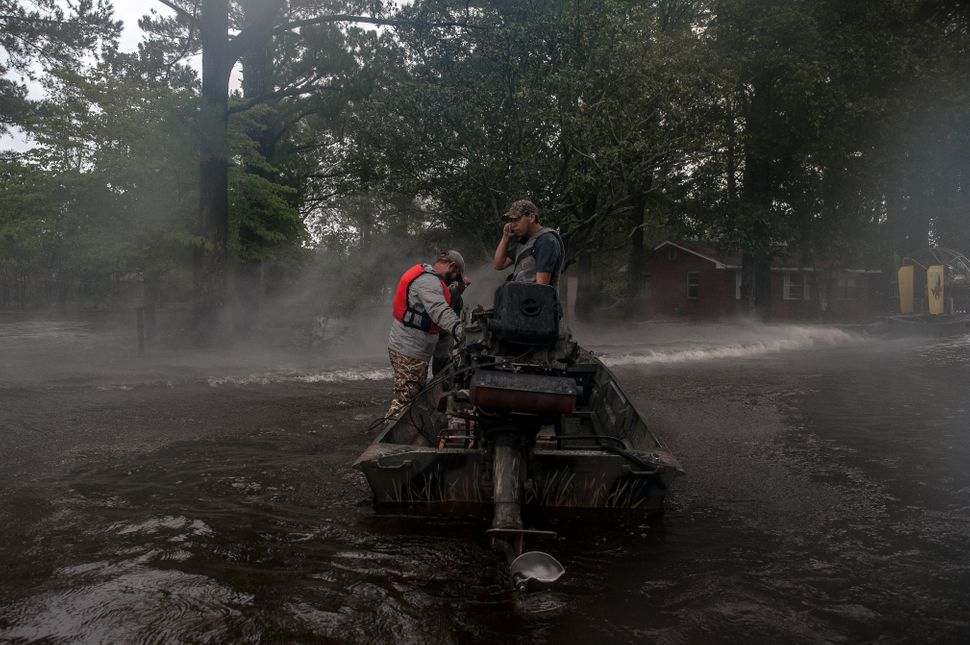 Rescuers with the Cajun Navy shield their faces from the spray off a fan boat as they prepare to enter a flooded neighborhood