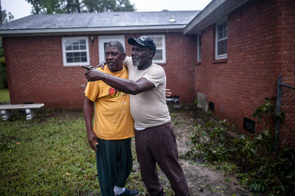 Ronnie McRae and Lorenzo Mitchell watch rising floodwaters in Lumberton, North Carolina, on Sunday.