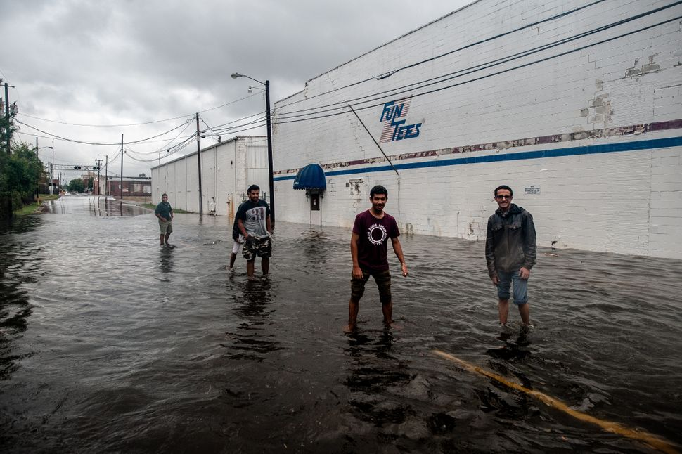 Residents of Lumberton walk through floodwaters near downtown as the Lumber River rises on Sunday.