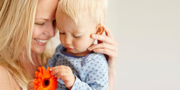 A loving mother holding her son as he looks at an orange flower