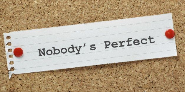 The phrase Nobody's Perfect typed on a piece of lined paper pinned to a cork notice board