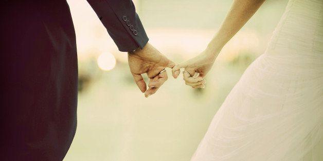 The hands of a marriage. Linked fingers two boyfriends after a wedding.Las manos de un matrimonio. Enlazados los dedos de dos novios tras una boda.