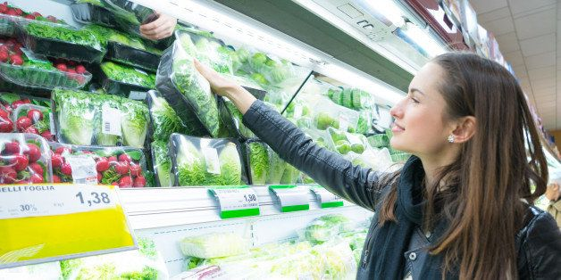 Woman in supermarket at vegetable shelf shopping for groceries.