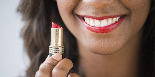Black woman holding lipstick