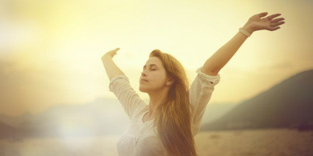 freedom concept, woman with arms raised in sunset field.
