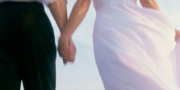 Rear view of a newlywed couple walking on the beach