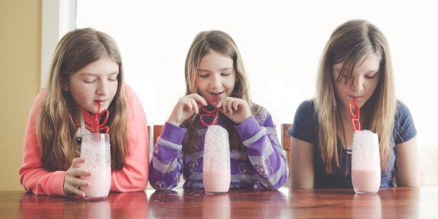 Caucasian girls drinking milk with curled straws at table