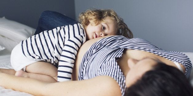 Little girl and pregnant mother lying together on bed