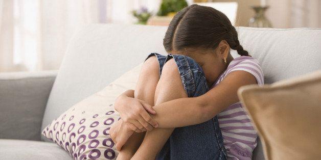 Sad Hispanic girl sitting on sofa