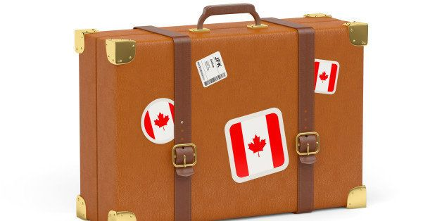 Travel suitcase with flag of canada isolated on white