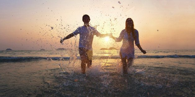 happy couple enjoy sunset on the beach
