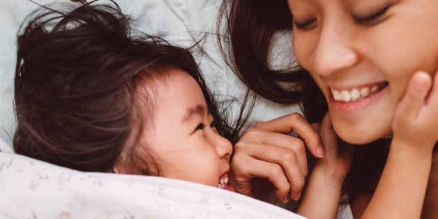 Lovely toddler girl putting her hands around her pretty young mom's face, while both looking at each other smiling joyfully on the bed after woke up in the morning.
