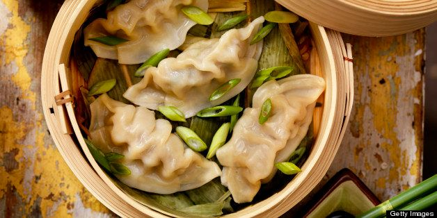 Steamed Dumplings in a bamboo steamer with bamboo leaves, fresh green onions, soya sauce and rice -Photographed on Hasselblad H1-22mb Camera