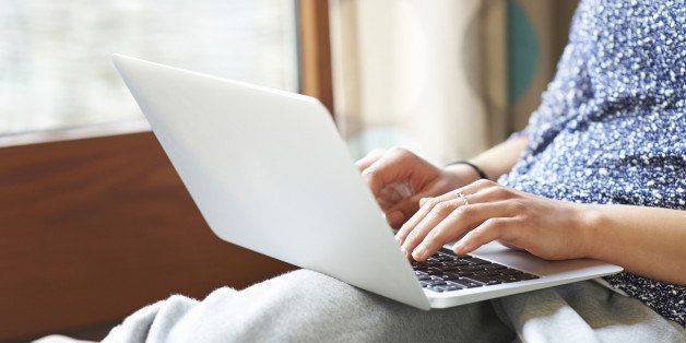 Woman using laptop at home, close up.