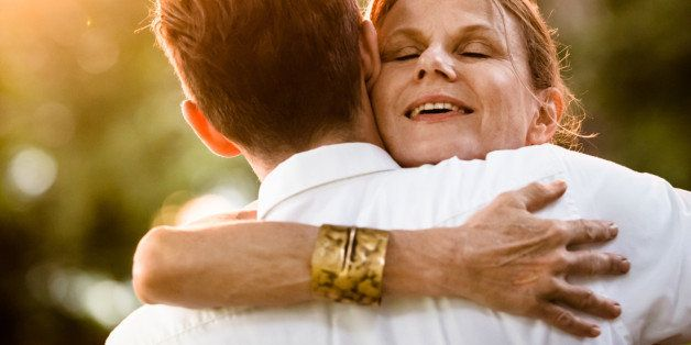 Close-up of a happy mature woman hugging a man at a garden party