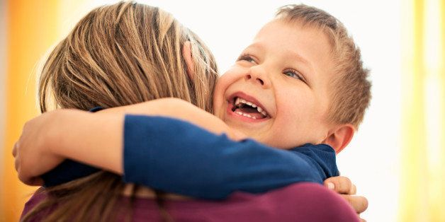 Close up portrait of mother and son hugging. The boy is laughing with joy and both ar backlit by the sunlight coming from the window behind them.